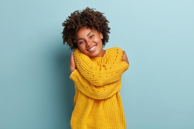 분홍색 스웨터에 포즈를 취하는 아프리카와 사랑스러운 여자