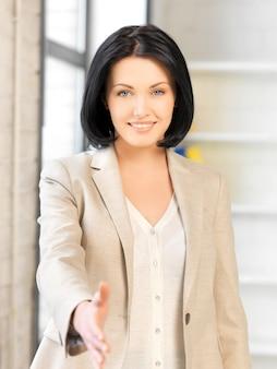 握手の準備ができている開いた手を持つ素敵な女性。