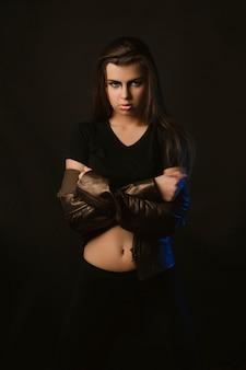스튜디오에서 포즈를 취하는 갈색 가죽 재킷에 예술 화장을 한 사랑스러운 여성