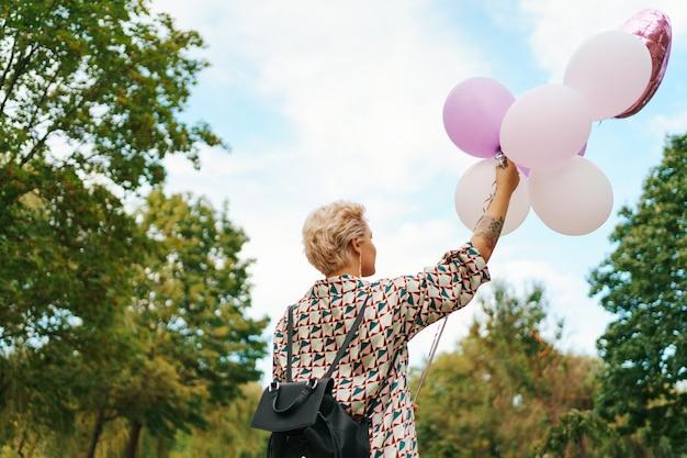 公園でピンクの風船で幸せに歩いているバックパックを持つ素敵な女性。自由と健康な女性のコンセプトです。