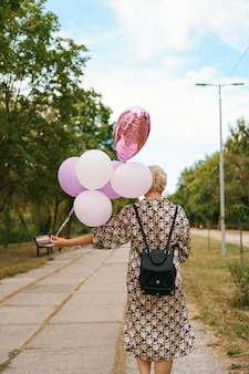 Lovely woman with backpack walking happy with pink balloons in the park. freedom and healthy women concept.