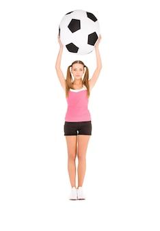 흰 벽에 큰 축구 공을 가진 사랑스러운 여자