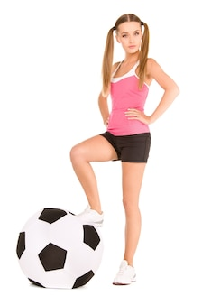 Lovely woman with big soccer ball over white wall