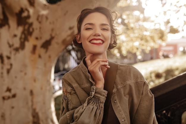 야외에서 웃 고 데님 재킷에 갈색 머리 짧은 헤어 스타일으로 사랑스러운 여자. 밖에 서 포즈를 취하는 붉은 입술으로 매력적인 여자.