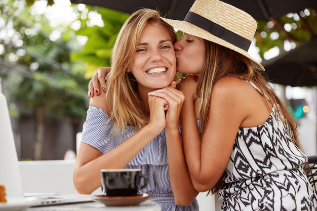 Lovely woman with cheerful expression happy to receive kiss from her girlfriend, sit together at coffee shop, use modern laptop for online communication, demonstrate devoted love to each other