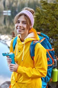 Bella donna con felice espressione facciale, vestita di impermeabile giallo, porta zaino