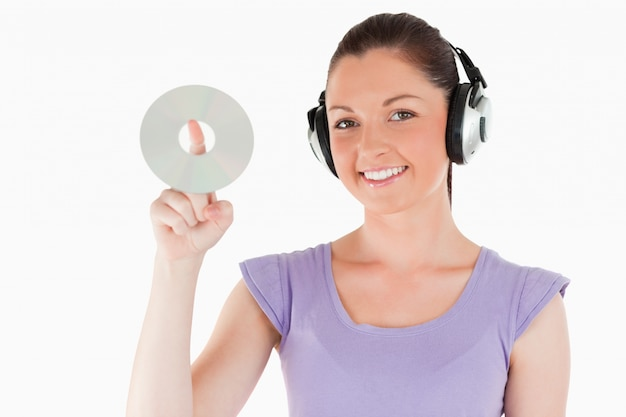 Lovely woman with headphones holding a cd while standing