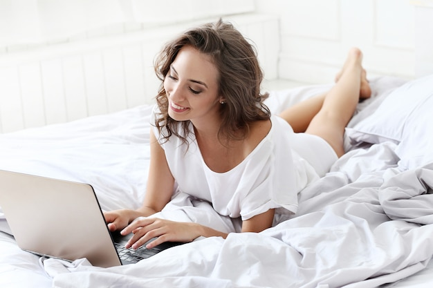 Lovely woman with laptop in the bed
