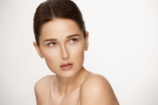 Lovely woman with nude mua looking to the top, copy space, gorgeous female with brown eyebrows and glossy lips