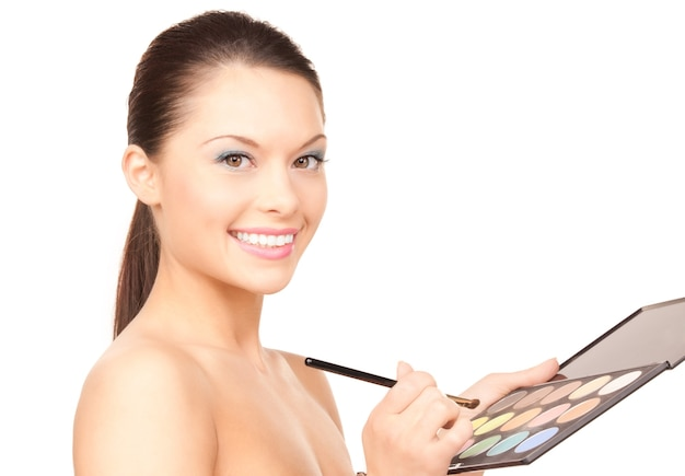 Lovely woman with palette and brush over white