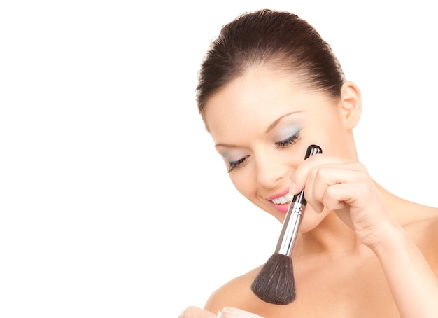 Lovely woman with powder and brush over white