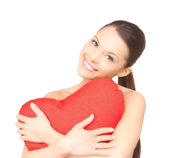 흰 벽에 빨간 하트 모양의 베개와 사랑스러운 여자