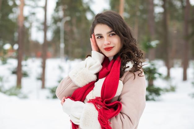 雪の降る冬にポーズをとる赤い口紅の素敵な女性。空きスペース