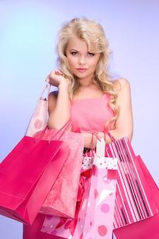 青の上の買い物袋を持つ素敵な女性