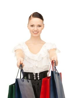 Милая женщина с хозяйственными сумками над белой