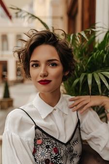 レストランのスタイリッシュなブラウスで短い髪の素敵な女性。明るい唇を持つ魅力的な女性がカフェで微笑む。