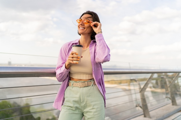 風の強い夏の日にモダンな橋の上を歩く短い髪型の素敵な女性