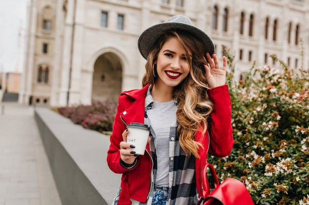 Lovely woman with shy smile waving hand on architecture wall