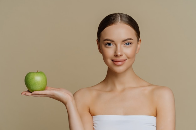 Lovely woman with stand wrapped in bath towel holds green apple