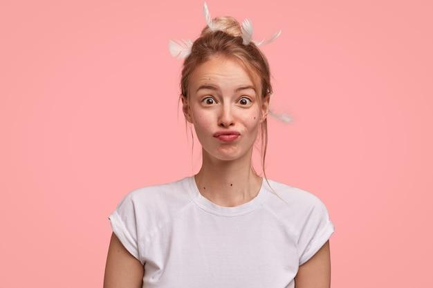 Bella donna con espressione sorpresa, fa una smorfia, si chiede qualcosa, ha dormito troppo, vestita casualmente, isolata su un muro rosa