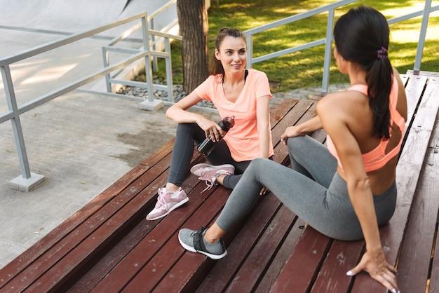 スポーツウェアの素敵な女性がスポーツグラウンドのベンチに座って話し、ボトルから水を飲む