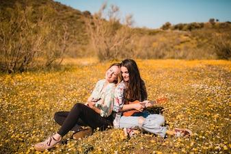 Lovely women with ukuleles in meadow