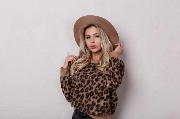 ヴィンテージのヒョウのセーターのポーズで革のズボンのエレガントなベージュの帽子でセクシーな唇と美しい目を持つ素敵な素晴らしい若い女性