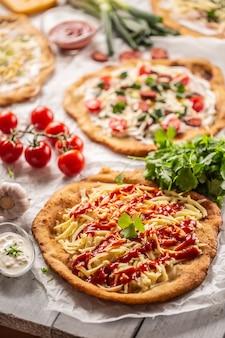 Прекрасный деревянный стол, полный хрустящих венгерских ланго, поданных с сыром, овощами, ветчиной, кетчупом, соусами, сливками, чесноком и сезонными продуктами.