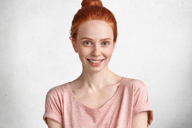 Милая молодая очаровательная улыбающаяся рыжая модель, одетая небрежно, без макияжа, демонстрирует свою естественную красоту, рада сфотографироваться