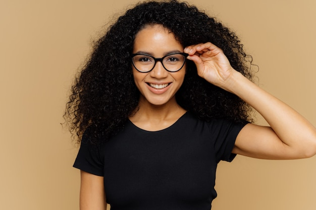 Lovely young african american woman grins at camera, keeps hand on rim of spectacles