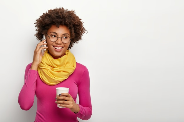 Lovely young african american woman has cheerful expression, has telephone conversation, drinks takeout coffee, glad expression, wears transparent round glasses, yellow scarf and pink turtleneck