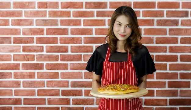 빨간 줄무늬 앞치마를 입은 셰프인 사랑스러운 젊은 아시아 여성이 벽돌 벽 근처에 서서 전통 이탈리아 음식을 맛있게 먹도록 설득하기 위해 맛있는 요리된 피자 나무 접시를 웃으면서 들어올립니다.