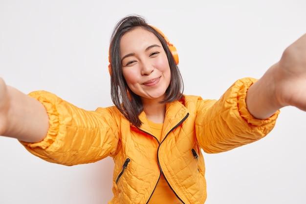 Милая молодая азиатская женщина с темными волосами делает селфи-портретные улыбки и слушает музыку, одетая в оранжевый анорак