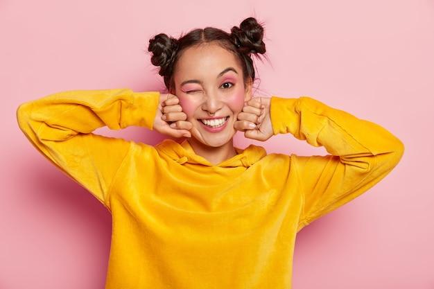 幸せな表情、まばたき、前向きな笑顔、屋内で楽しい、2つの髪の結び目を持つ素敵な若いアジアの女性