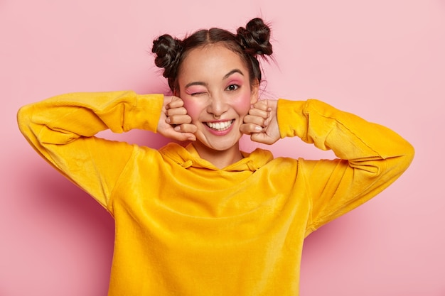 Lovely young asian woman with happy face expression, blinks eye and smiles positively, has fun indoor, two hair knots