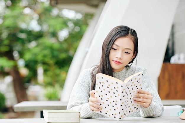 屋外のテーブルで面白い本を読んで楽しんでいる素敵な若いアシナ10代の少女