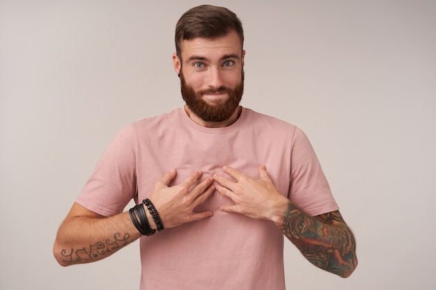 Bel giovane barbuto maschio dagli occhi azzurri con tatuaggi che sembra colpevole con le labbra piegate, tenendo le mani sul petto e dispiaciuto per qualcosa, isolato su bianco