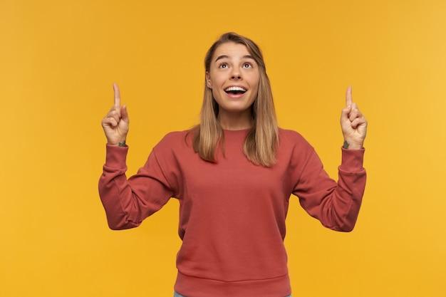 Милая молодая красивая женщина широко улыбается и показывает пальцем на copyspace, позирует со счастливым выражением лица, носит красный пуловер и синие джинсовые брюки