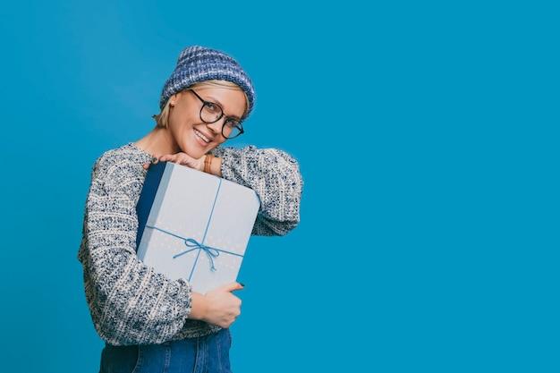 Прекрасная молодая блондинка женщина, одетая в синюю одежду, глядя в камеру, смеясь, держа синюю подарочную коробку на синем фоне.