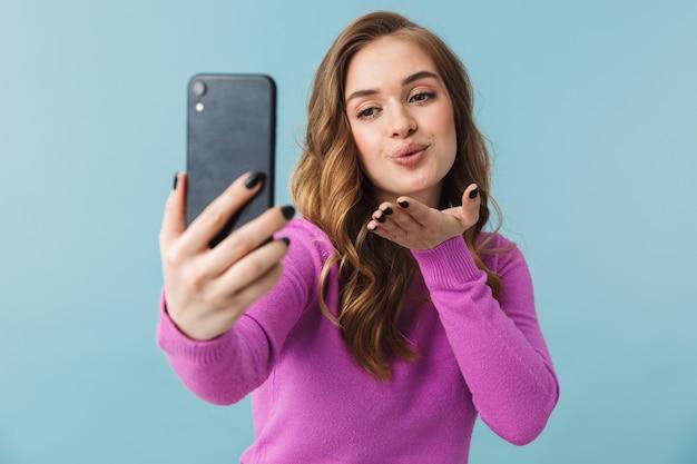 青い壁に孤立して立って、自分撮りをして、キスを送る素敵な若いブロンドの女性