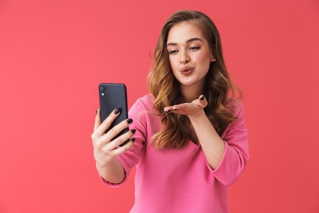ピンクの壁に孤立して立って、自分撮りをして、キスを送る素敵な若いブロンドの女性