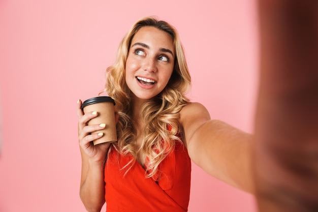 ピンクの壁の上に孤立して立っている夏のドレスを着て、自分撮りを取り、テイクウェイカップを保持している素敵な若いブロンドの女性