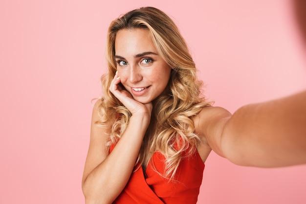 ピンクの壁に孤立して立っている夏のドレスを着て、自分撮りをしている素敵な若いブロンドの女性