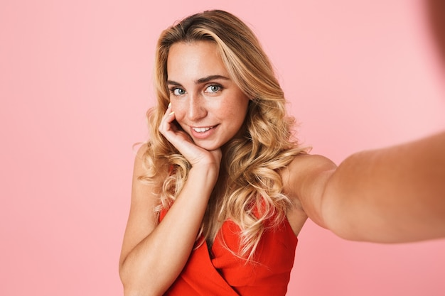 Lovely young blonde woman wearing summer dress standing isolated over pink wall, taking a selfie