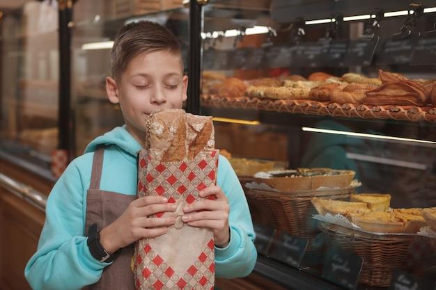 그의 가족 빵집 가게에서 신선한 빵 냄새, 앞치마를 입고 사랑스러운 어린 소년