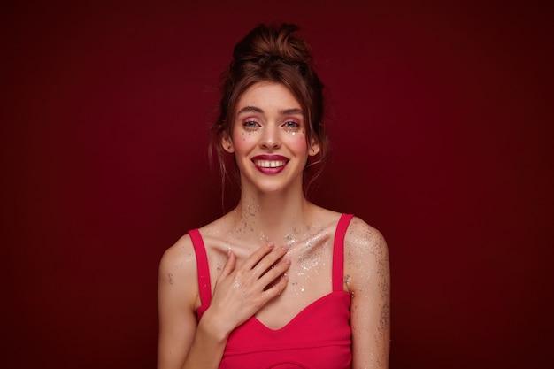 Bella giovane donna dai capelli castani in top rosa con cinghie mantenendo il palmo sul petto e sorridendo dolcemente, indossando i capelli annodati e avendo trucco da sera mentre posa