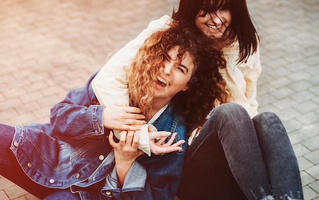 街の地面に座って笑いながら巻き毛で彼女の親友を抱きしめる素敵な若いブルネット。