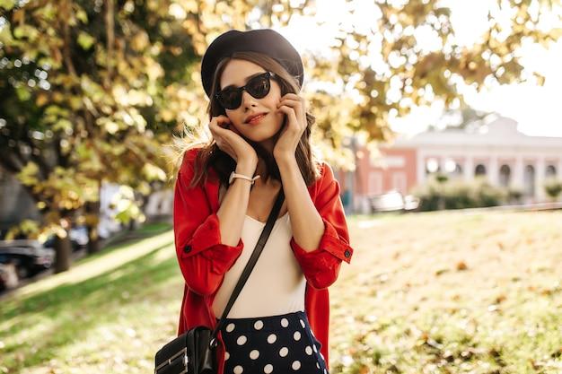 베레모, 흰색 탑, 빨간 셔츠, 검은 색 선글라스를 쓴 사랑스러운 젊은 갈색 머리가 야외에서 포즈를 취하고 얼굴을 만지고 있습니다.