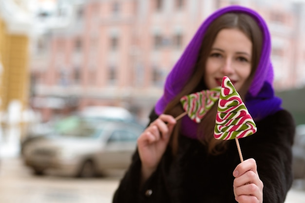 Lovely young  brunette woman in purple scarf holding colorful christmas sweets. blur effect
