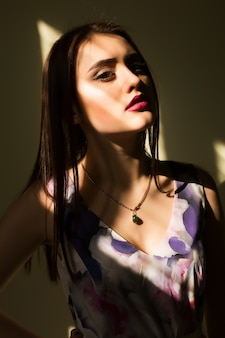 太陽の光と暗い部屋でポーズをとって明るい化粧の素敵な若いブルネットの女性